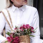 Mit Blumen in der Korbtasche